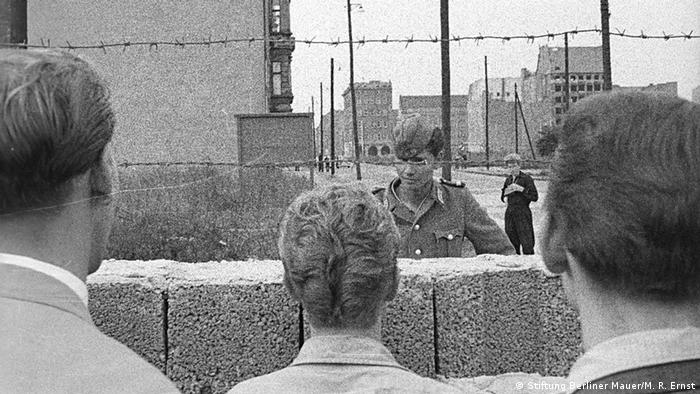 A solider stands on one side of the Berlin wall as it is under construction while people look on (Stiftung Berliner Mauer/M. R. Ernst)