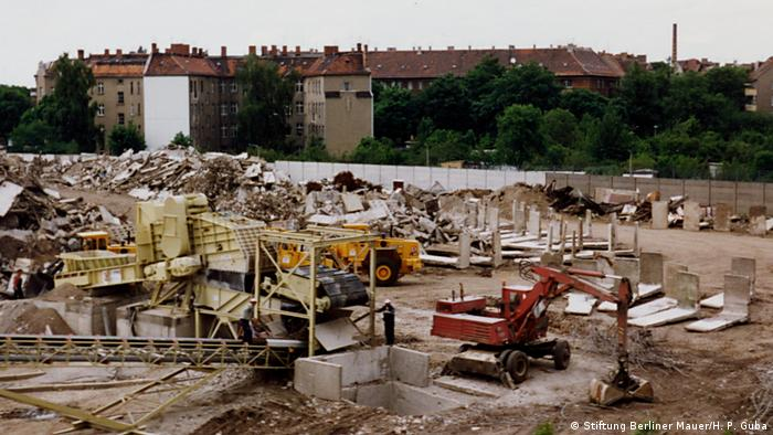 A bulldozer and trucks break down pieces of the Berlin Wall (Stiftung Berliner Mauer/H. P. Guba)