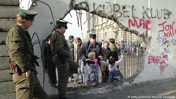 A man and woman help two children climb through a hole in the wall as border police look on (Stiftung Berliner Mauer/E. Kasperski)