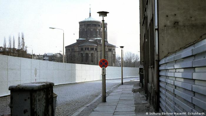 The Berlin wall snakes along a street in front of St. Thomas Church (Stiftung Berliner Mauer/M. Schuhhardt)
