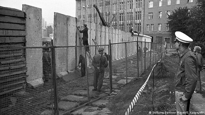 Workers patch the cracks between the concrete segements as the new Berlin Wall gets installed while a West policeman looks on (Stiftung Berliner Mauer/E. Kasperski)