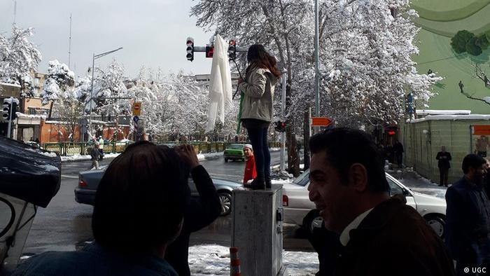 Manifestante segura hijab na ponta de um galho em sinal de protesto