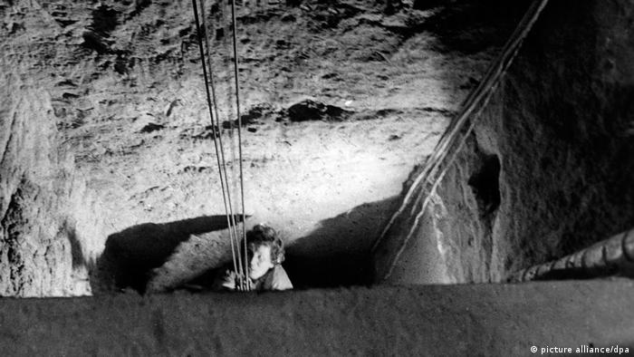 A woman emerges from an escape tunnel in West Berlin in 1964.