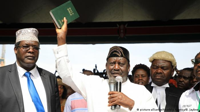 Rail Odinga holds up a Bible in one hand and two microphones in another
