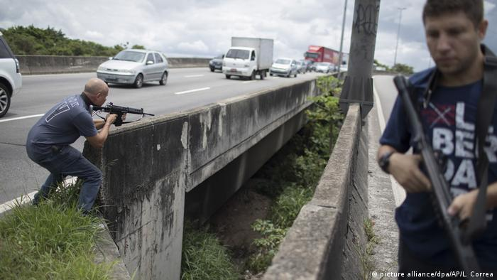 Police officer points a rifle to an area below a busy overpass