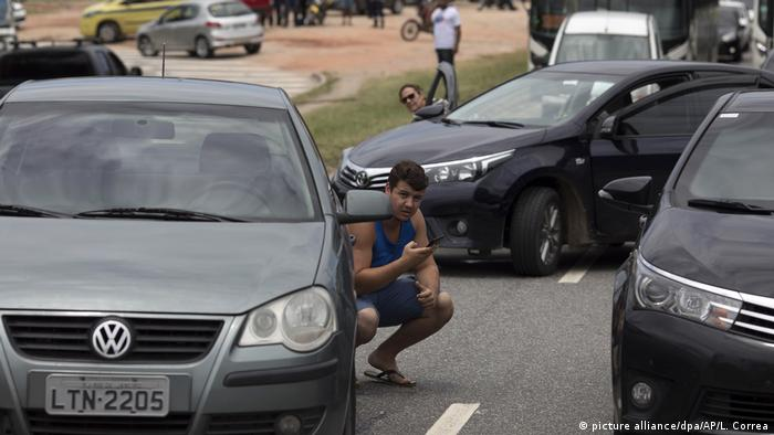 Man crouching behind a car during the shootout (picture alliance/dpa/AP/L. Correa)