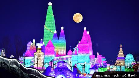 Illuminated snow sculptures for the during 19th China Harbin Ice and Snow World are seen against the blood Supermoon in the sky in Harbin city, northeast China's Heilongjiang province