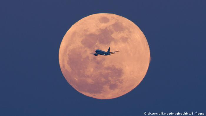 red moon with plane flying across it (picture-alliance/Imaginechina/S. Yipeng)