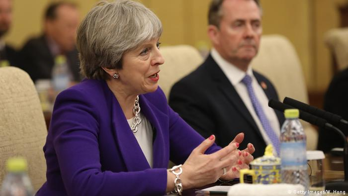 Theresa May with Liam Fox in background, in China