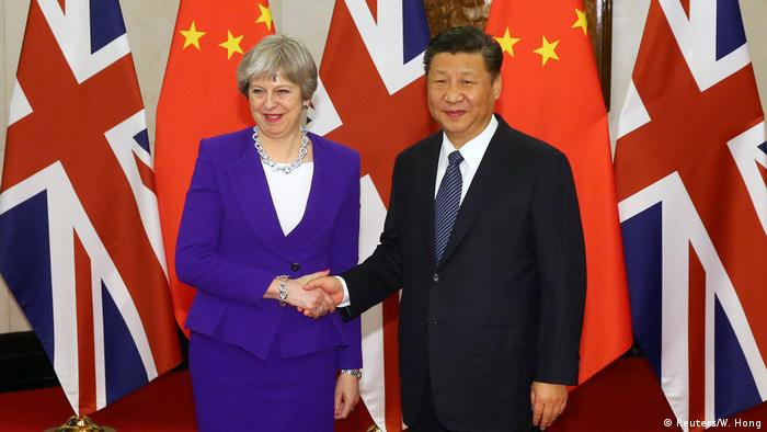 Chinese President Xi Jinping shakes hands with British Prime Minister Theresa May