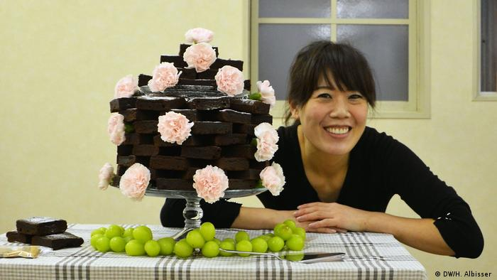 Ai Kojima poses behind a stack of brownies she baked for a wedding