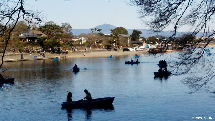 People paddle in boats on a lake near Kyoto