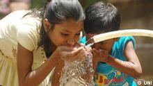 Kinder trinken Wasser aus einem Schlauch im indischen Patna