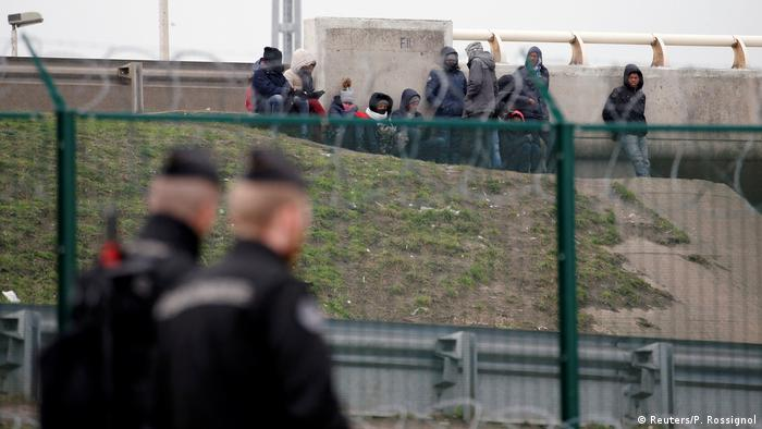 Migrants at Calais, police officers walking past
