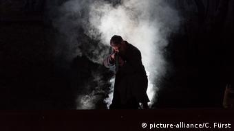 A still from a concert showing a man against a cloud of smoke