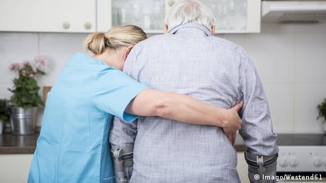 Caregiver supporting elderly man