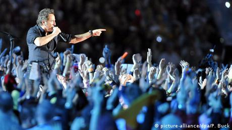 Springsteen performing on stage surrounded by a large crowd at the 2009 Super Bowl.