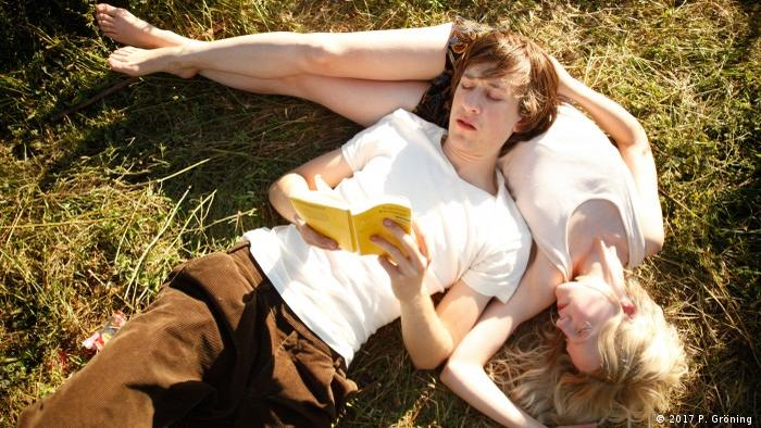 Filmstill with a brother and a sister lying in the grass of 'My Brother's Name is Robert and He is an Idiot' by Philip Gröning (2017 P. Gröning )