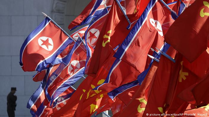 North Korean and Workers' Party flags flutter as a soldier walks by (picture-alliance/dpa/AP Photo/W. Maye-E)