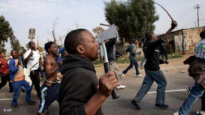A xenophobic mob armed with carrying axes and shovels (AP)