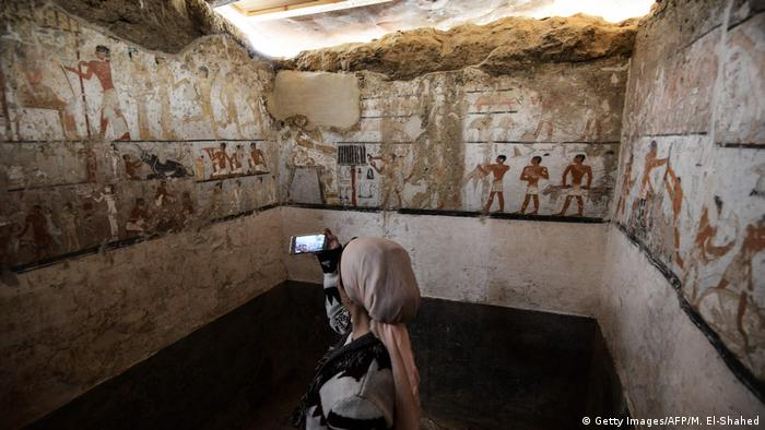 A woman takes a photo inside the tomb of an Old Kingdom priestess adorned with well-preserved and rare wall paintings on the Giza plateau in Cairo (Getty Images/AFP/M. El-Shahed)