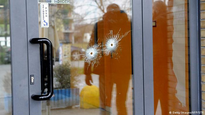 Bullet holes are seen in a glass door as police forensics officers carry out investigations following a drive-by shooting in Macerata