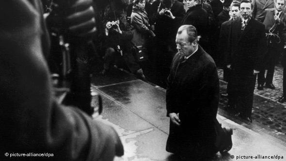 Willy Brandt kneels before a Holocaust memorial in front of a crowd of onlookers