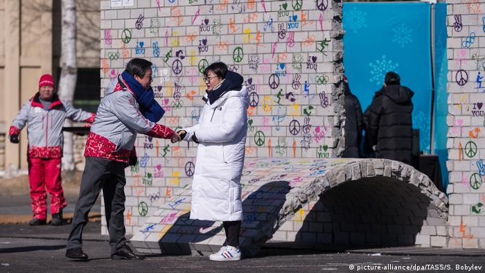 Люди приветствуют друг друга в олимпийской деревне