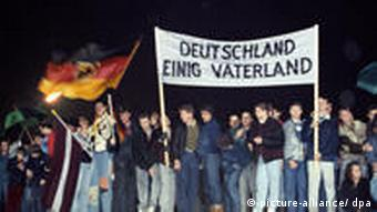 Berliners sing and dance on top of the Berlin Wall in 1989