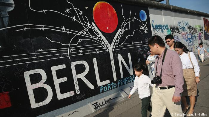 Visitors from China walk past murals on the former Berlin Wall at the East Side Gallery on August 5, 2014 in Berlin, Germany