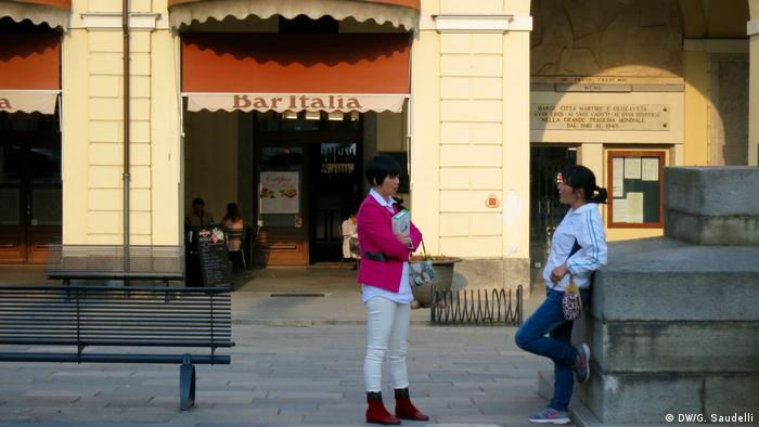 Chinese women chat in the main square of Barge, Italy
