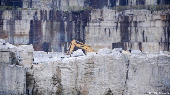 A bulldozer perches at the top of a quarry on the Punta Ostentata mountain near Bagnolo Piemonte, Italy