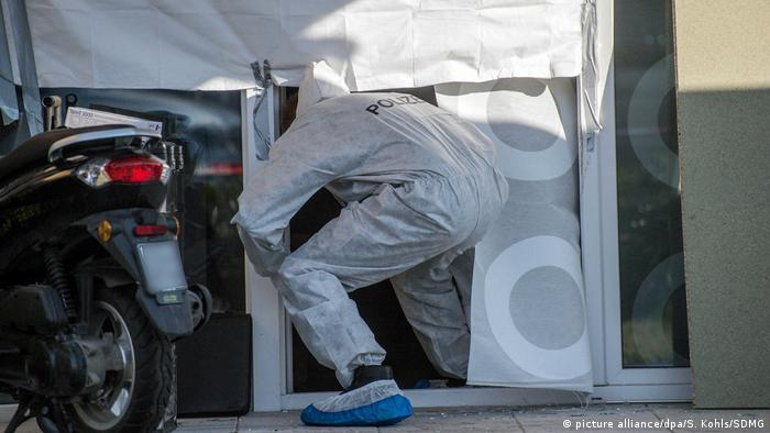 Police worker enters the Esslingen house where a family of four was found dead
