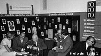 Several readers sit at a stand at Frankfurt's Book Fair in 1960 for Rowohlt
