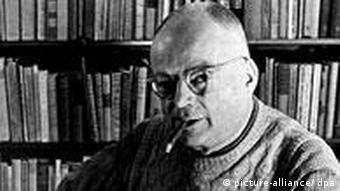 Publisher Ernst Rowohlt sits at a desk in front of a large shelf of books
