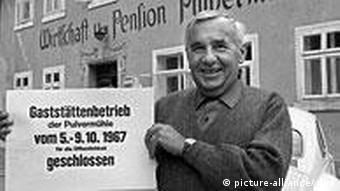 Der Vorsitzende der Gruppe 47, Hans Werner Richter, steht vor der Pulvermühle in Waischfeld/Oberfranken und zeigt ein Schild, dass Schließung der Gaststätte für das normale Publikum anzeigt, Oktober 1967.