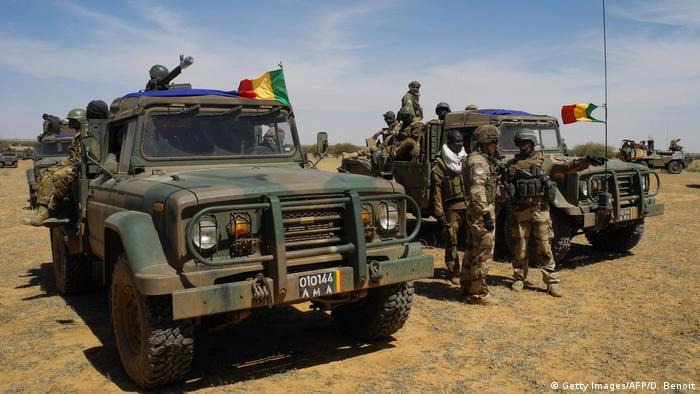 Mali soldiers stand next to military trucks