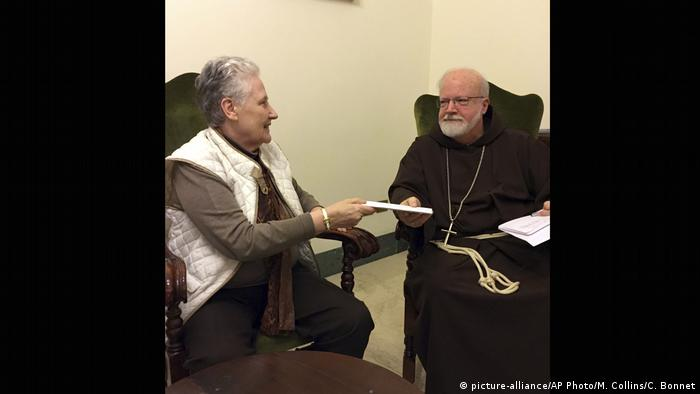 In this image, Marie Collins, a member of the pope's sex-abuse commission, hands a letter detailing the abuse of Juan Carlos Cruz to Cardinal Sean O'Malley in 2015. Collins later quit the commission, citing 'shameful' resistance from Vatican officials.