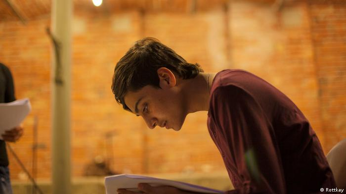 young boy reads from manuscript