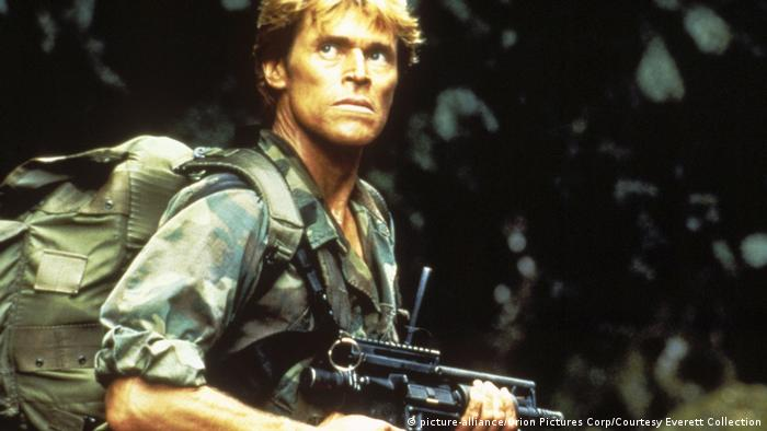 Willem Dafoe im Film Platoon, 1986, als Soldat mit Gewehr und Rücksack. Er blickt nach oben. (picture-alliance/Orion Pictures Corp/Courtesy Everett Collection)