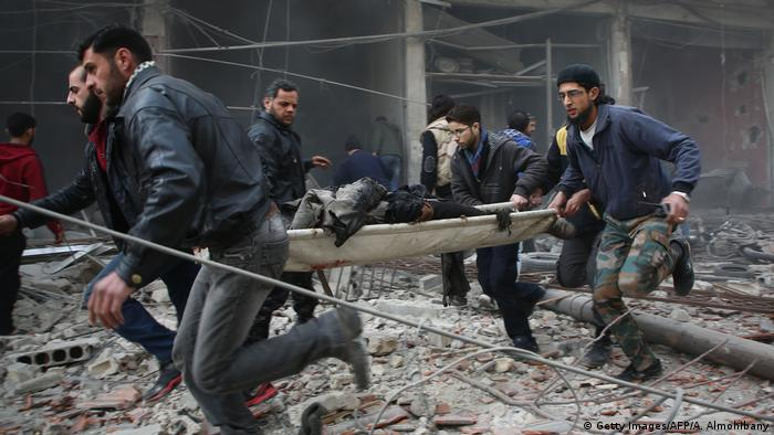 Syrian rescuers evacuating badly injured people following an airstrike