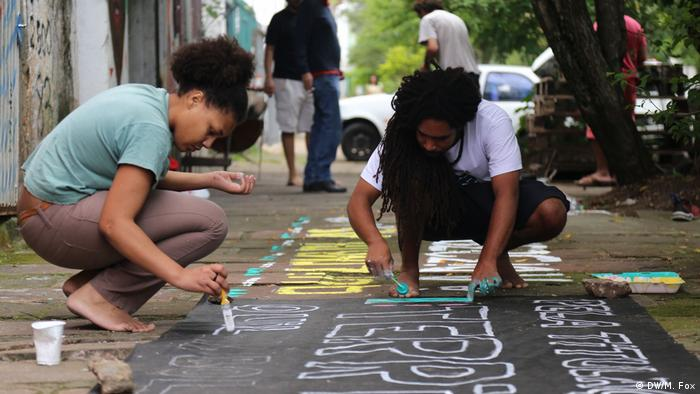 Tamirez Diaz paints a banner in support of quilombo rights in Porto Alegre, Brazil