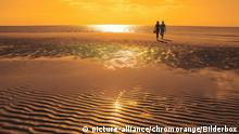 Paar am Strand bei Sonnenuntergang | Verwendung weltweit