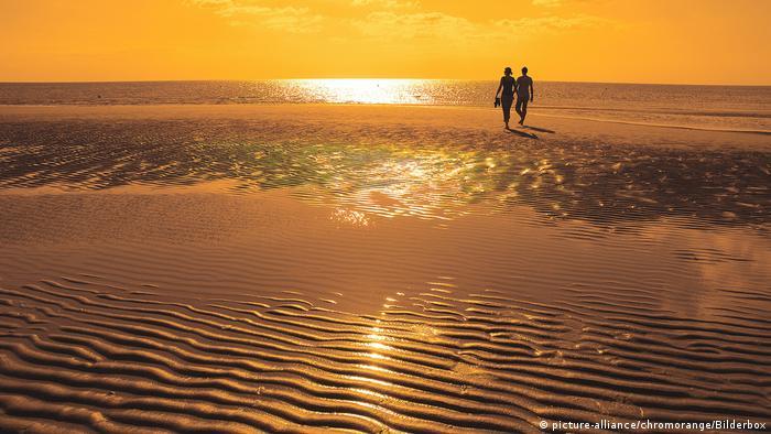 Paar am Strand bei Sonnenuntergang (picture-alliance/chromorange/Bilderbox)