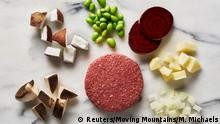 The Moving Mountains B12 Burger, pictured surrounded by the ingredients: mushroom, coconut, soy beans, beetroot, potato and onion. Photo Credit: Moving Mountains