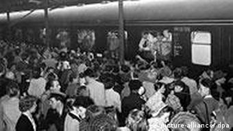 Tausende Menschen bereiten der deutschen Fußballnationalmannschaft am 05.07.1954 auf dem Bahnhof einen begeisterten Empfang, um die in einem Sondertriebwagen heimreisende DFB-Mannschaft zu begrüßen und zu feiern. Aus dem rechten Wagenfenster schauen die Spieler (v.l.) Max Morlock, Jupp Posipal und Paul Mebus heraus.