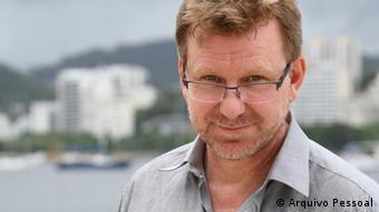 Louro, de óculos e com barba rala, Thomas Milz olha sorridente para a câmera (fundo desfocado: cidade do Rio de Janeiro)