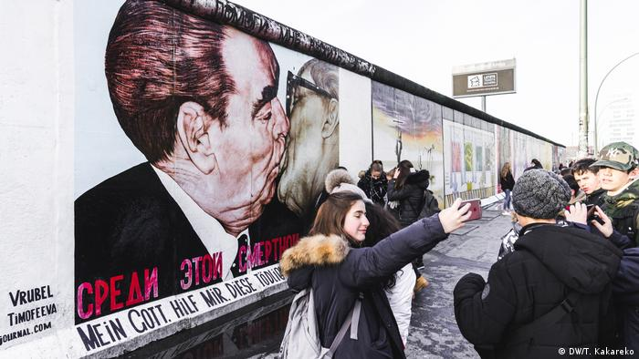 Young tourists pose for pictures in from of the famous Brezhnev-Honecker motif Bruderkuss or Brotherly Kiss by Russian artist Dimitrji Vrubel at the East Side Gallery, in Berlin (DW/T. Kakareko)