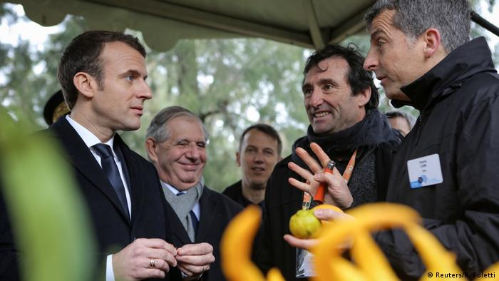 French President Emmanuel Macron (L) listens to scientists as he visits the National Institute for Agronomic Research of San-Giuliano near Bastia, on the French Mediterranean island of Corsica.