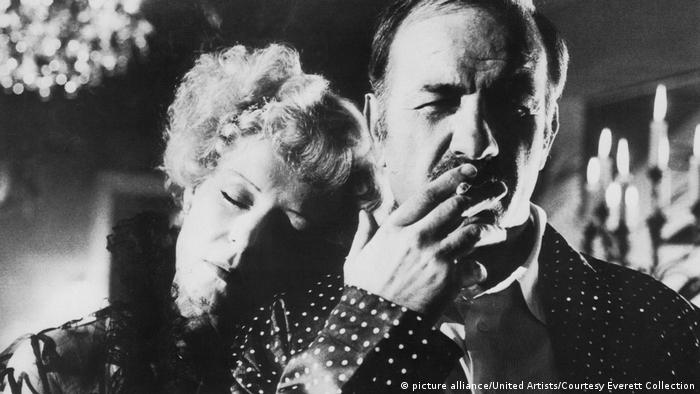 A man smokes a cigarette, a woman lays her head on his shoulder: film still from 'Veronika Voss' (picture alliance/United Artists/Courtesy Everett Collection)